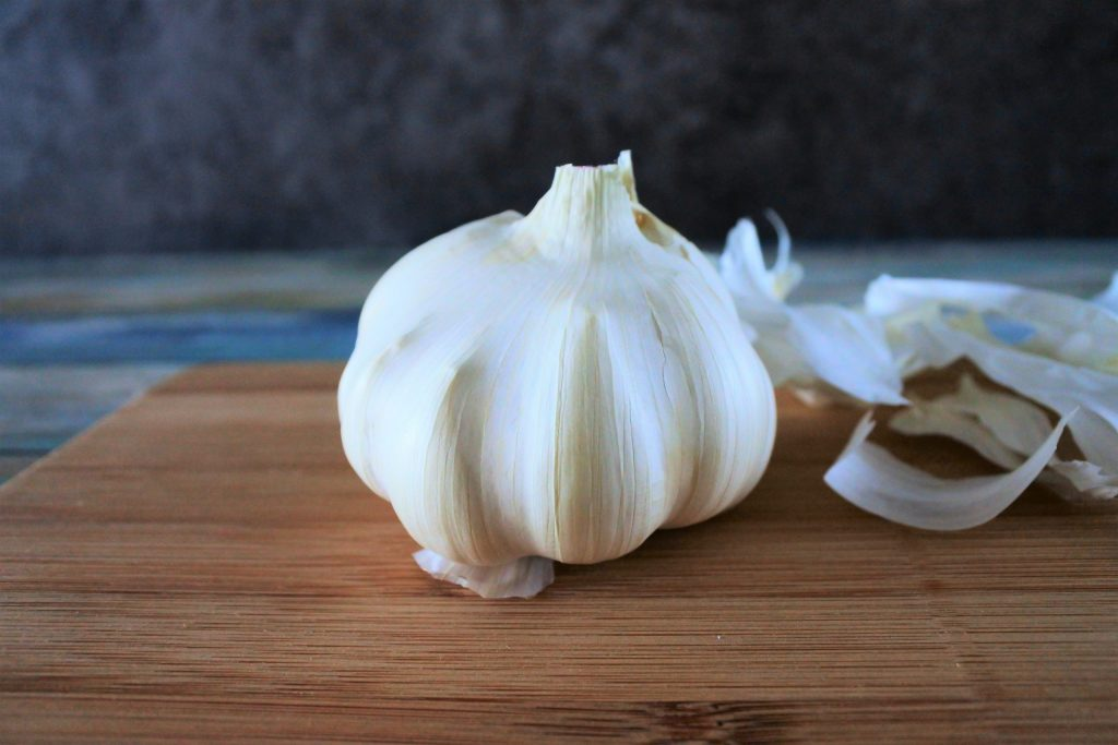A head on image of a head of garlic on a wooden board with layers of outer skin peeled off and on the right side of the board