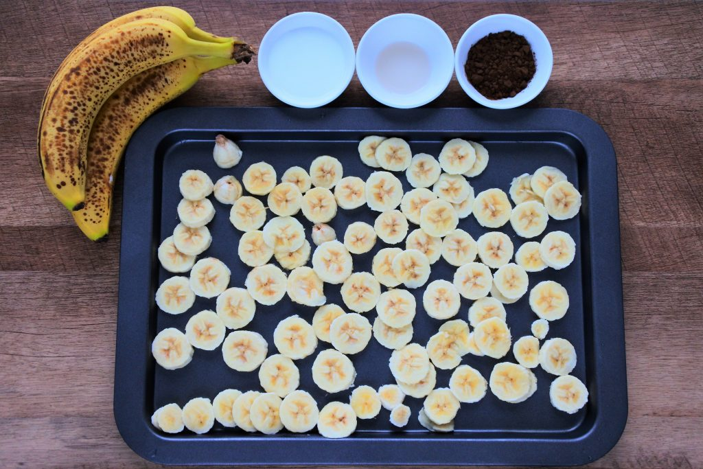 An overhead image of a tray of sliced frozen bananas with a whole banana in the top left corner and three dishes containing coconut milk, vanilla extract and cocoa powder
