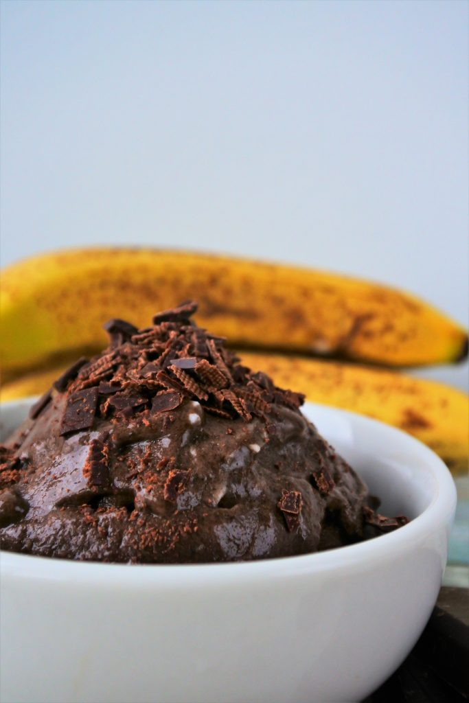 A close up image of a chocolate ice cream topped with shaved chocolate with some whole bananas in the background