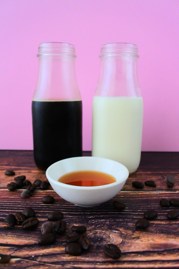 A head on image of a bottle of brewed black coffee, a bottle of whole milk and a small dish of maple syrup
