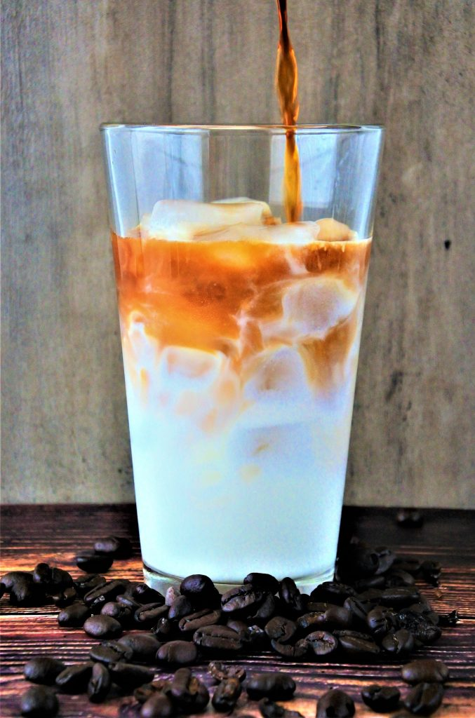 A close up image of a glass of milk with a stream of coffee being poured in surrounded by coffee beans on a wooden tabletop