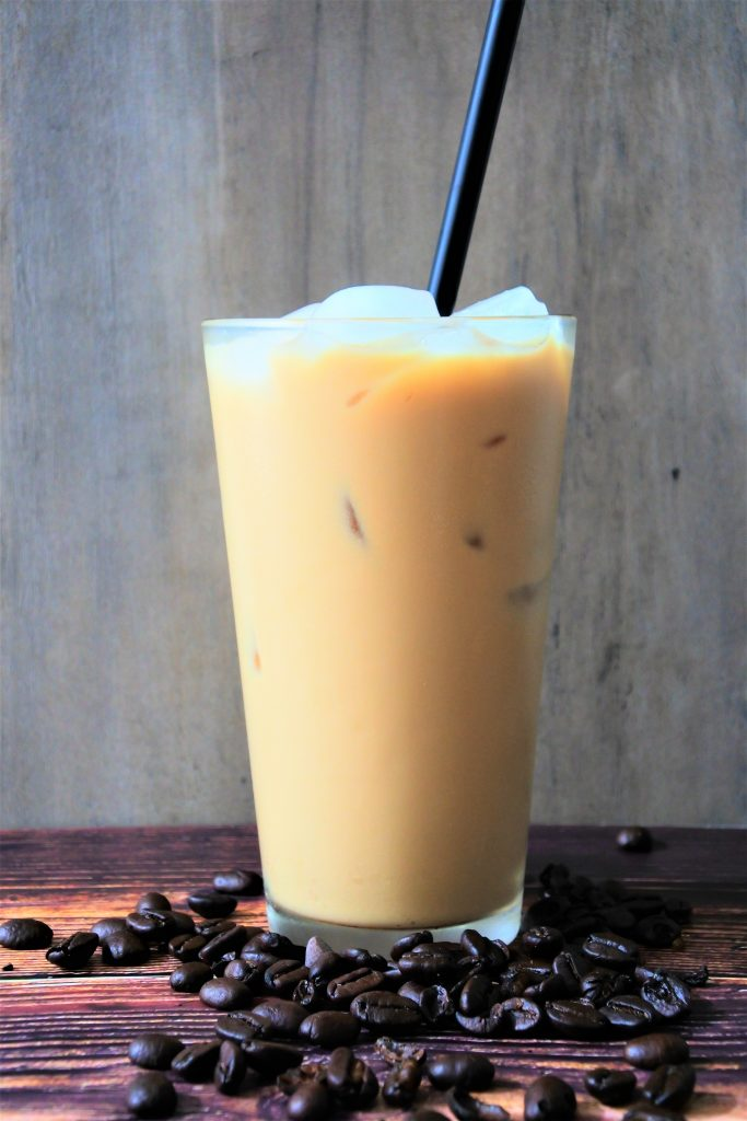 A glass of iced coffee with ice cubes and a black straw on a wooden table with whole coffee beans