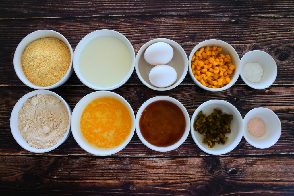 An overhead image of bowls containing ingredients for Jalapeno cornbread including corn meal, whole wheat pastry flour, buttermilk, melted butter, eggs, honey, sweet corn kernels, diced jalapenos, baking powder and salt.