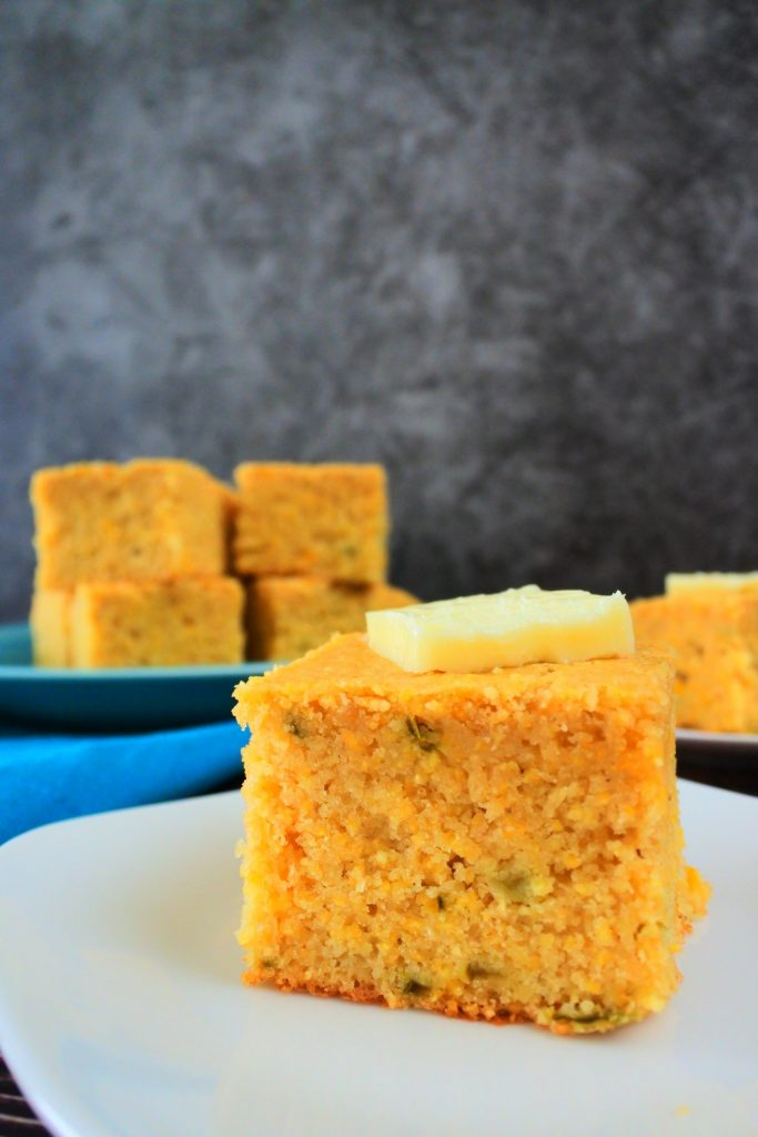 A head on image of a piece of jalapeno cornbread on a plate topped with a pat of butter with a plate of cornbread pieces in the background
