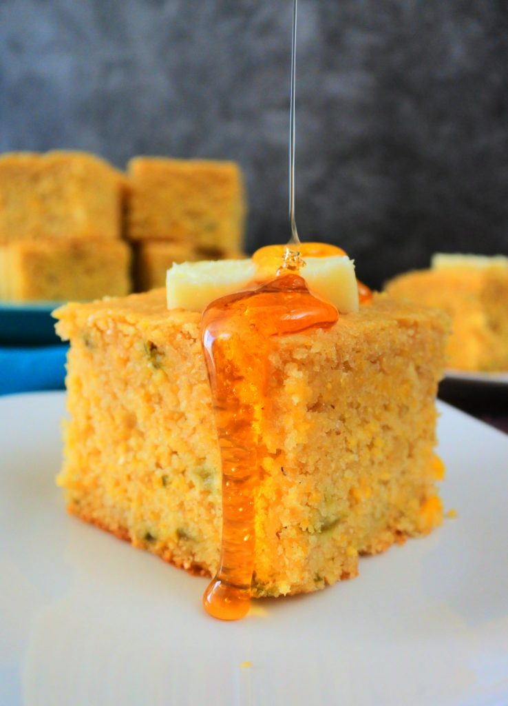 A head on image of a piece of jalapeno cornbread on a plate topped with a pat of butter and a drizzle of honey that spilled over the sides with a plate of cornbread pieces in the background