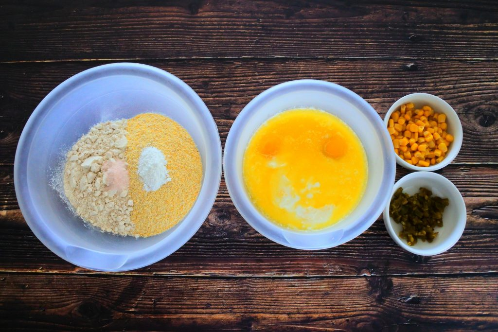 And overhead image of bowls containing unmixed wet ingredients, dry ingredients and two smaller bowls of sweet corn kernels and diced jalapenos