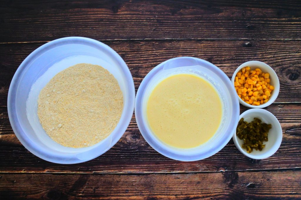 And overhead image of bowls containing wet ingredients, dry ingredients and two smaller bowls of sweet corn kernels and diced jalapenos