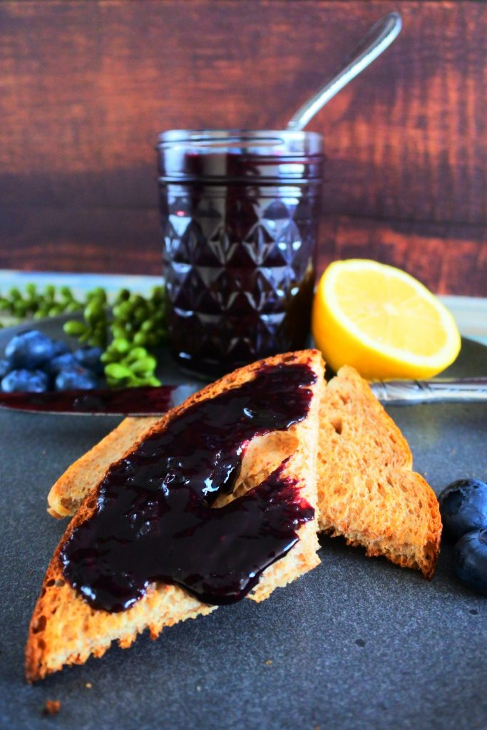 Head on image of a slice of jam coated toast with a jam covered knife behind it and a jar of blueberry jam in the background surrounded by fresh blueberries