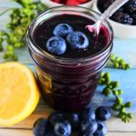 An angled image of a jar of blueberry jam with fresh blueberries on top and a spoon in it surrounded by fresh fruit including blueberries, raspberries, blackberries and a half cut lemon