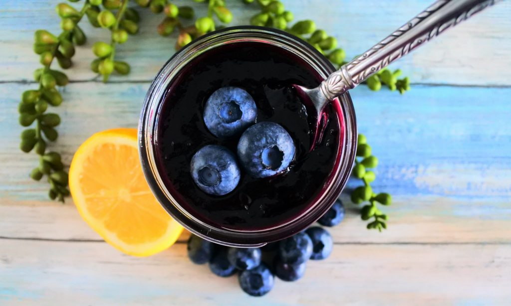 An overhead image of a jar of blueberry jam with a spoon in it and three fresh blueberries with more blueberries and half a lemon around the base