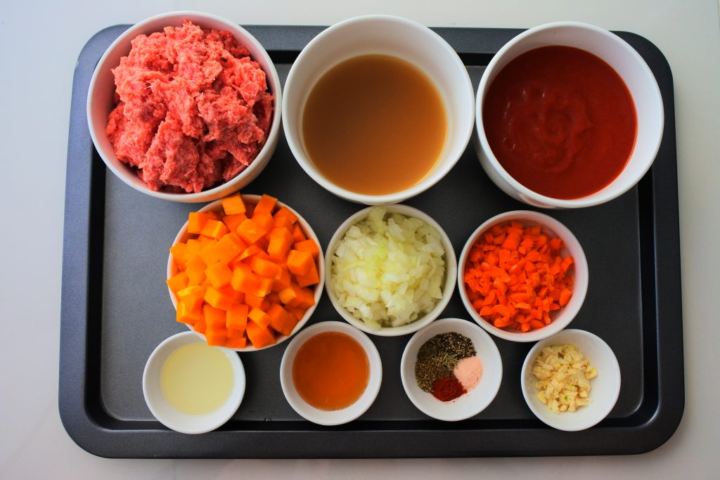 An overhead image of a tray of ingredients for the lasagna's meat sauce including: Meat, broth, tomato sauce, butternut squash, onions, carrots, olive oil, honey, salt, pepper, smoked paprika, dried basil, oregano, rosemary and diced garlic