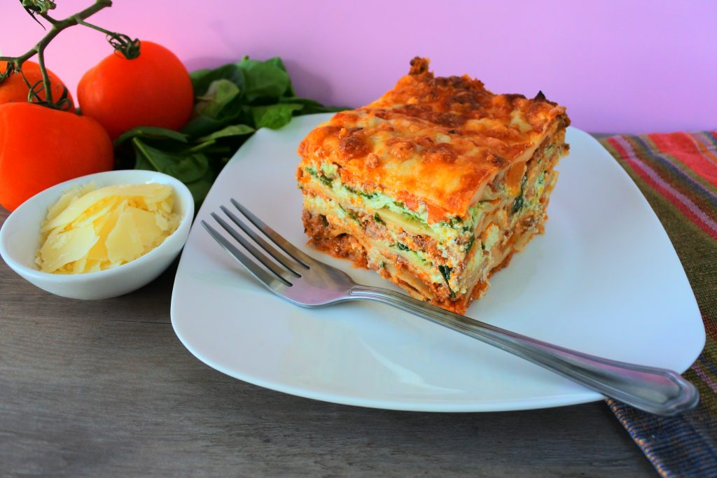 A head on image of a slice of lasagna on a plate with a fork and fresh spinach, tomatoes and a small dish of Parmesan on the side