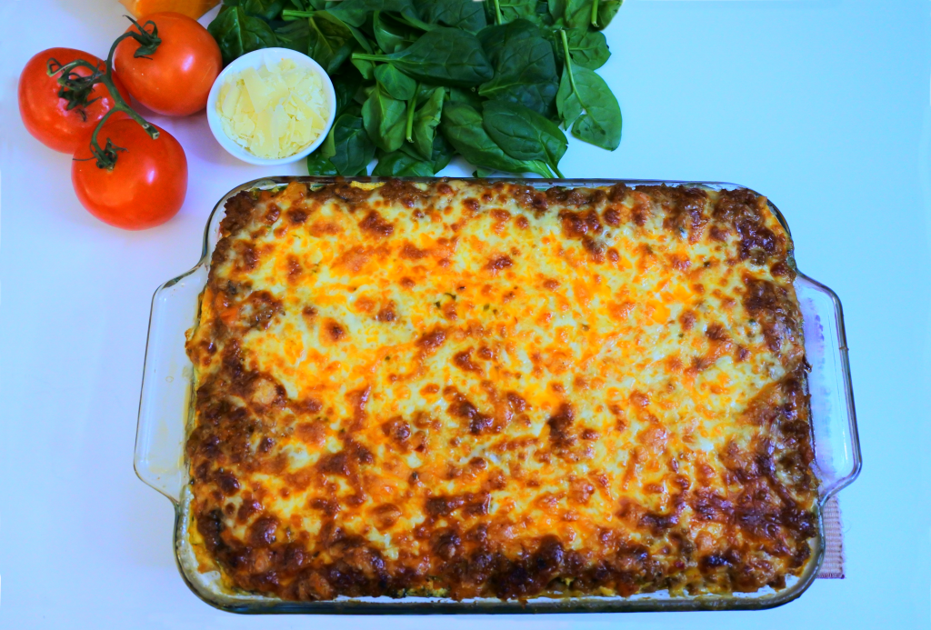 An overhead image of a baked clean eat lasagna with fresh spinach, tomatoes on the vine and a small dish of Parmesan in the top right corner