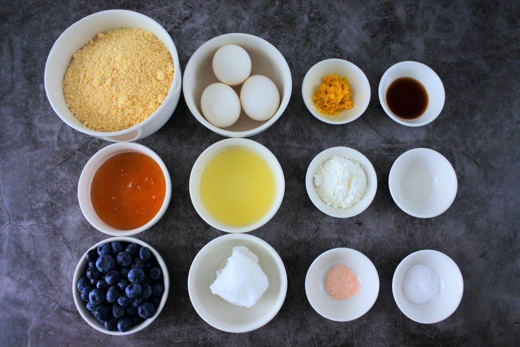 An overhead image of ingredients for a lemon-blueberry almond flour cake including: blanched almond flour, eggs, honey, fresh blueberries, lemon juice, coconut oil, lemon zest, vanilla extract, potato starch, lemon extract, Himalayan salt and baking soda