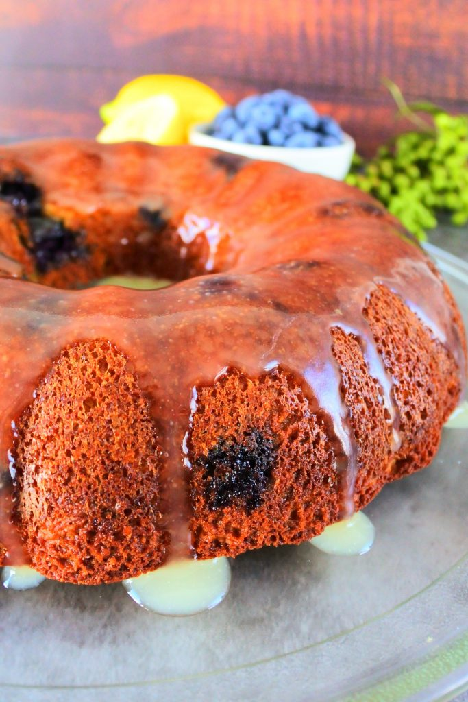 A close up of a glazed lemon blueberry bundt cake on a glass plate with fresh lemons and blueberries in the background