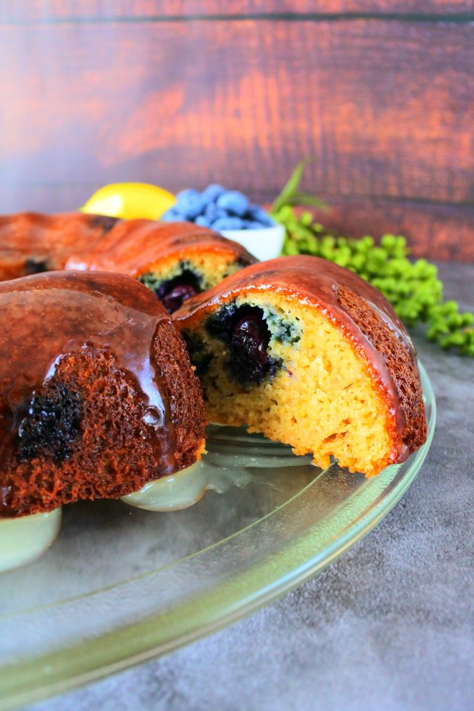 A close up of a cut glazed lemon blueberry bundt cake on a glass plate with fresh lemons and blueberries in the background