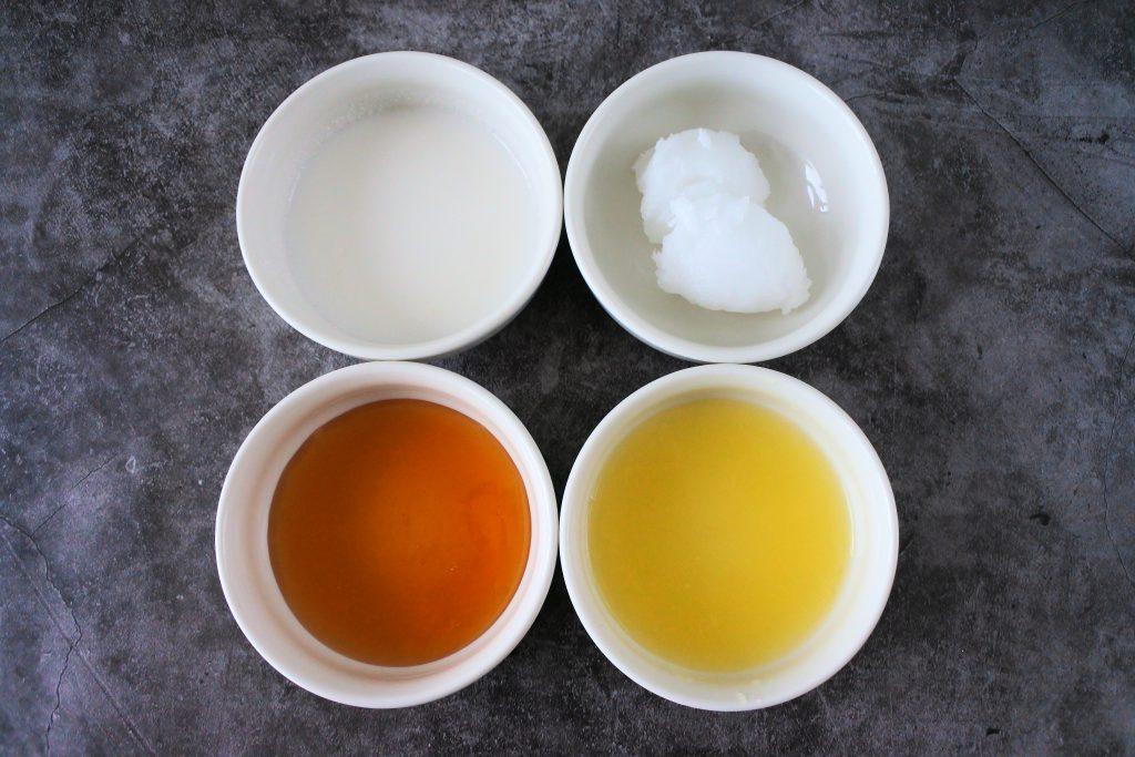 An overhead image of bowls of ingredients for a lemon glaze including coconut milk, coconut oil, honey and lemon juice