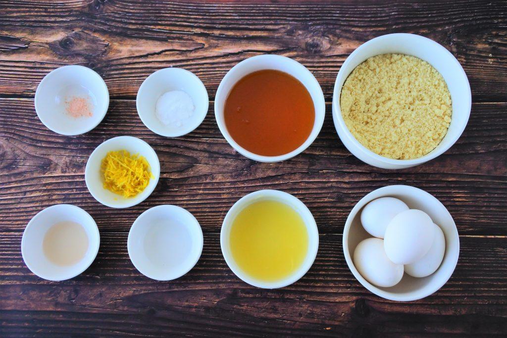 Overhead image of bowls containing the following ingredients: almond flour, eggs, honey, lemon juice, lemon zest, lemon extract, vanilla extract, salt, baking soda and baking powder