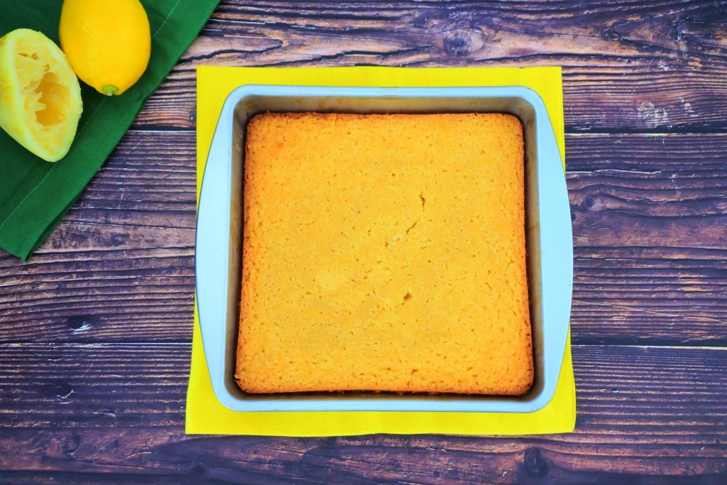 An overhead image of a square pan of baked lemon cake on a yellow napkin with fresh lemons on a green napkin in the top left corner