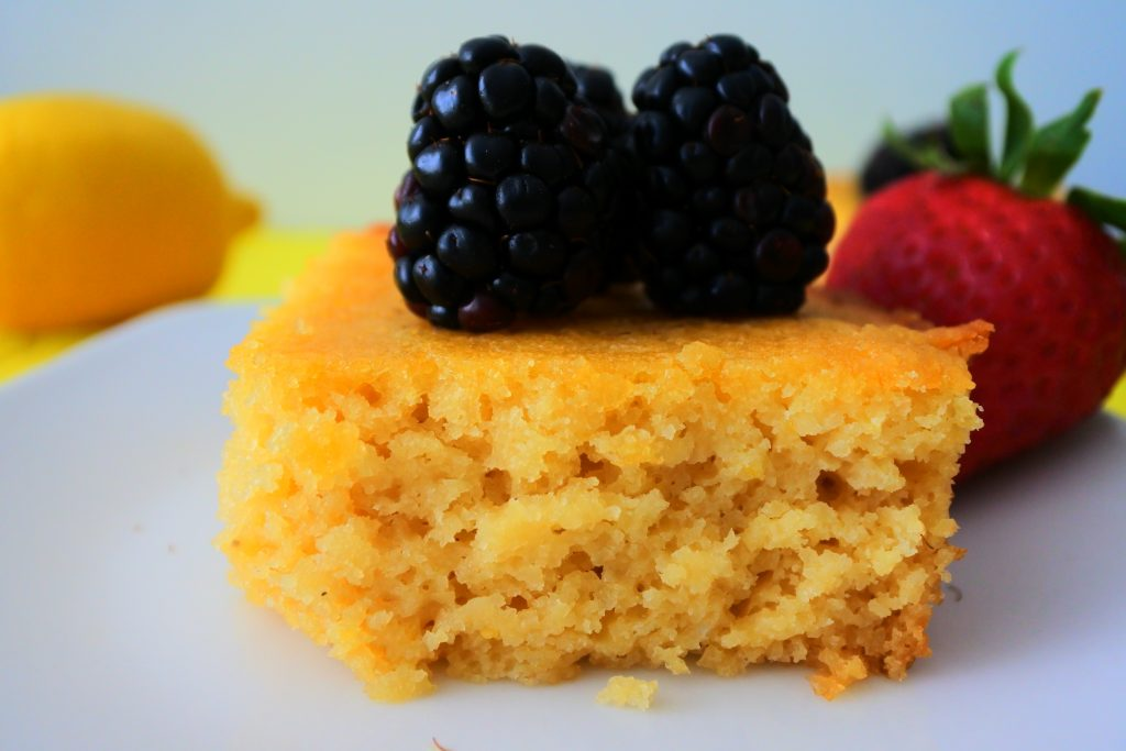 A close up image of a square of lemon cake topped with blackberries with a lemon and strawberry in the background