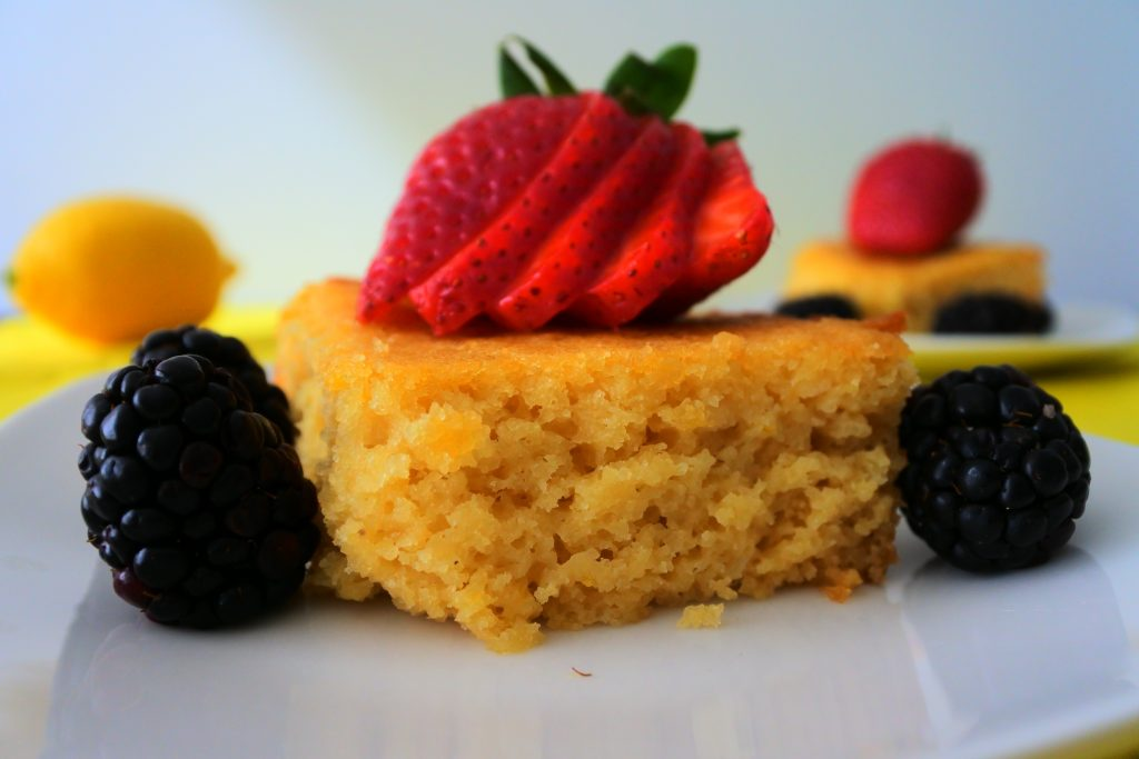 A close up image of a square of lemon cake topped with a sliced strawberry and surrounded by blackberries