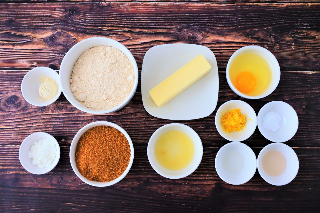 An overhead image of bowls of ingredients for lemon cookies including vital wheat gluten, whole wheat flour, potato starch, raw organic cane sugar, butter, lemon juice, an egg, lemon zest, baking powder, lemon extract and vanilla extract.