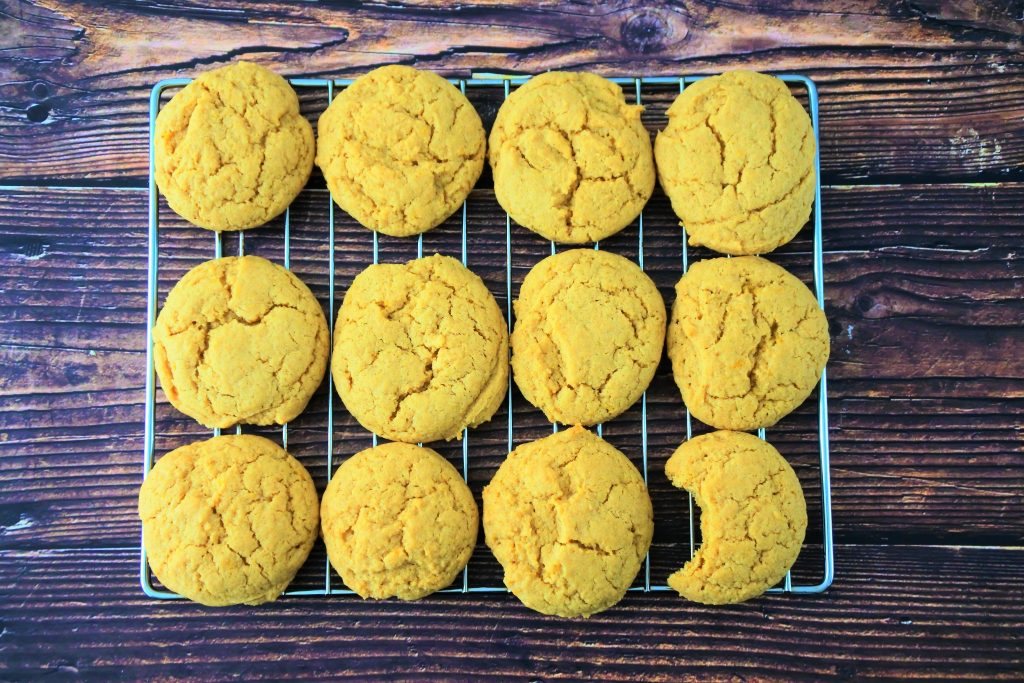 An overhead image of a wire rack of twelve lemon sugar cookies on a wood background with a bite taken out of the cookie in the lower right corner