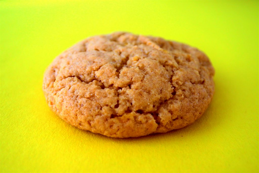 Close up image of a lemon sugar cookie with a cracked top on a yellow background
