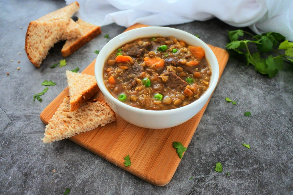 Close up image of a bowl of lentil and quinoa beef stew on a wood plank with pieces of bread on the side