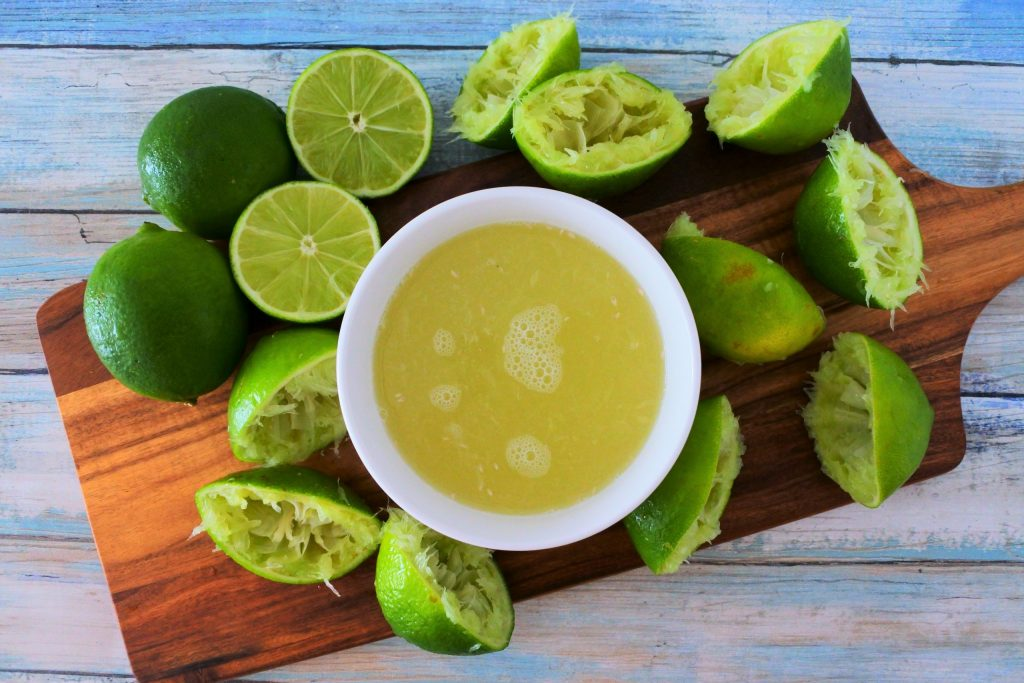 An overhead image of a bowl of freshly squeezed lime juice on a plank surrounded by fresh and squeezed limes