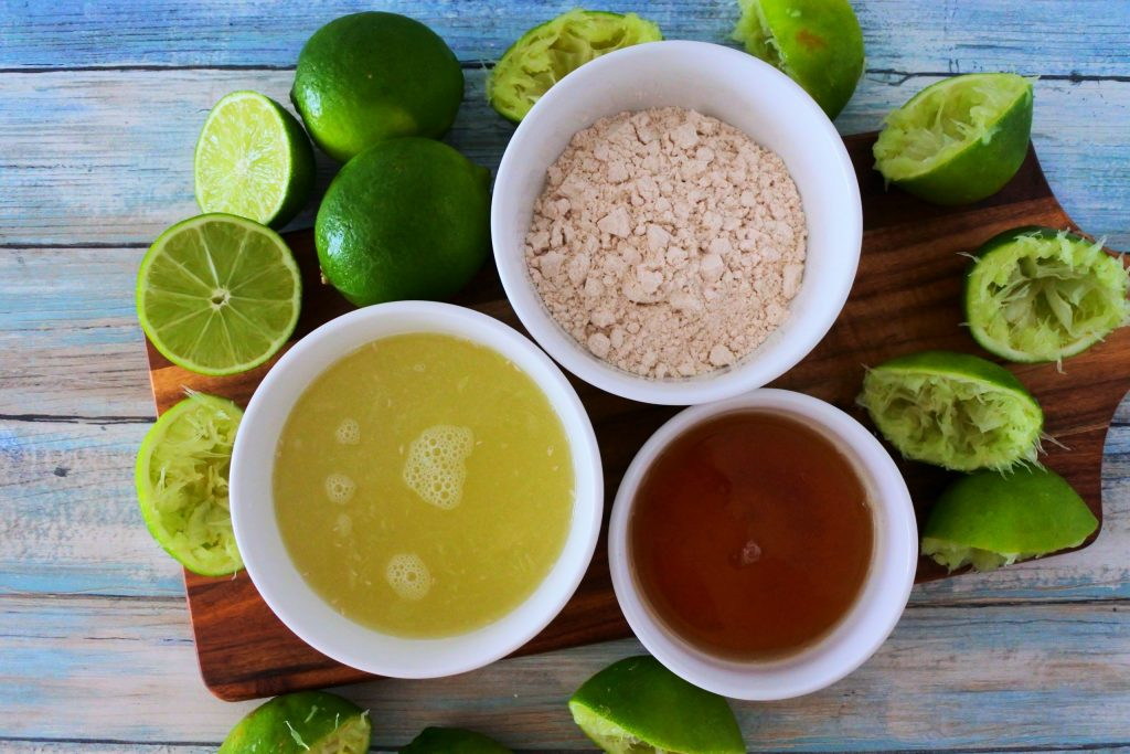 An overhead image of ingredients for a limeade including fresh lime juice, sugar and honey