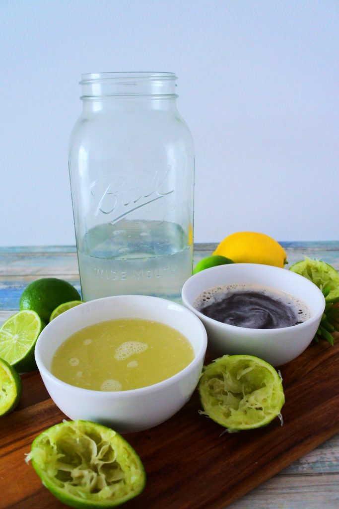 A head on image of ingredients for limeade including water, lime juice and a simple honey and sugar syrup surrounded by fresh limes