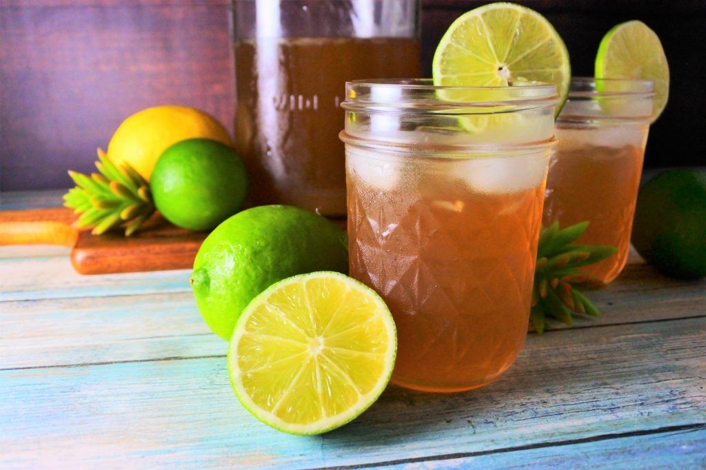 Head on image of jars of limeade served with ice surrounded by fresh limes