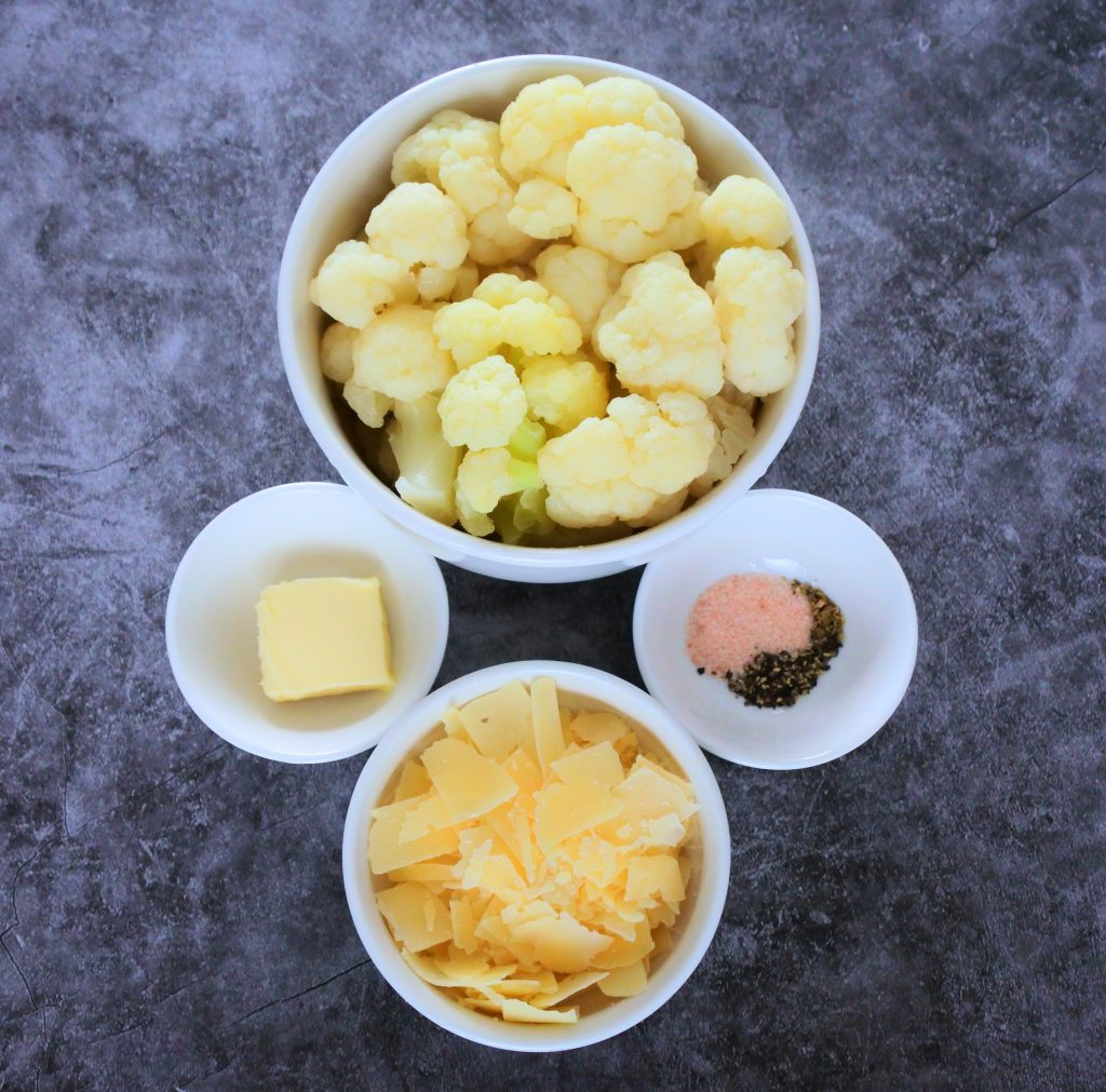 An overhead image of ingredients in bowls including steamed cauliflower florets, a pat of butter, salt and pepper and shaved Parmesan cheese
