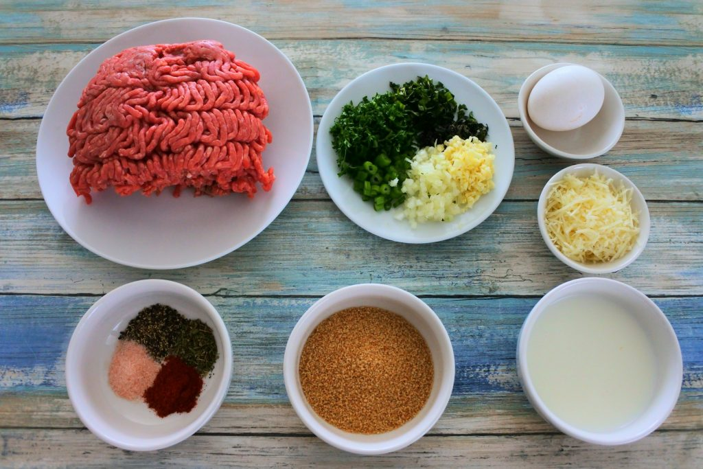 An overhead image of bowls of ingredients for meatballs including: ground beef, fresh herbs and spices, whole wheat breadcrumbs, milk, cheese and an egg.
