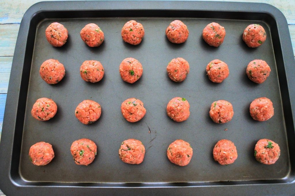 An overhead image of a tray of uncooked meatballs