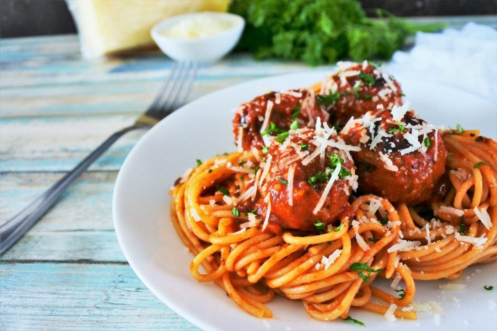 An angled image of a plate of spaghetti and meatballs garnished with freshly shredded cheese and parsley