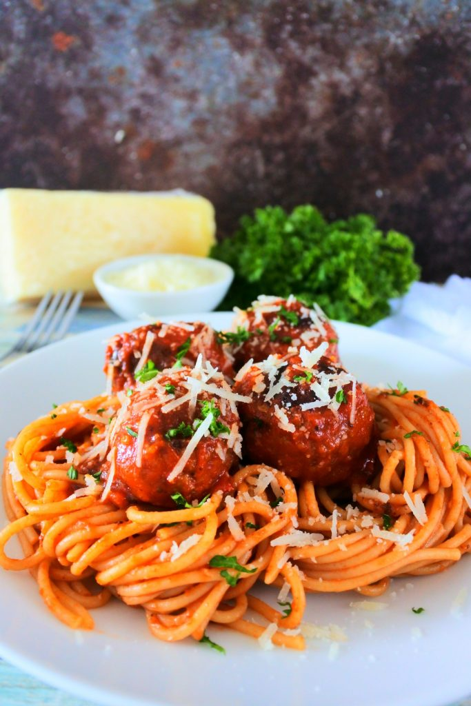 A head on image of a plate of spaghetti and meatballs garnished with freshly shredded cheese and parsley