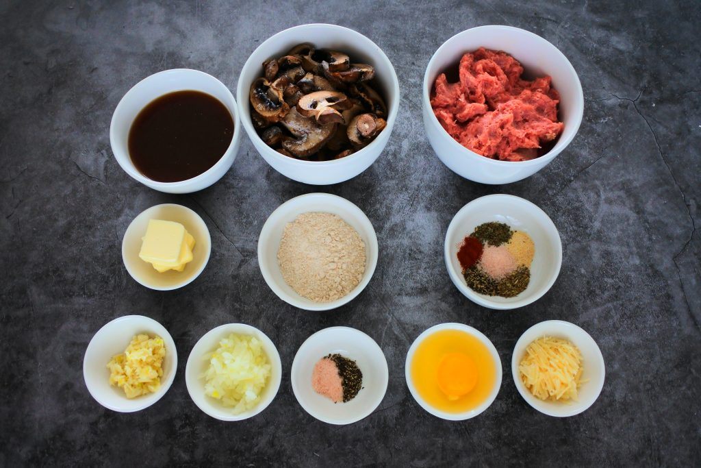 An overhead image of bowl containing ingredients including: ground turkey, an egg, Parmesan cheese, spices (salt, pepper, garlic powder, smoked paprika, dried basil and dried oregano), mushrooms, beef bone broth, whole wheat pastry flour, butter, garlic, onion, salt and pepper.