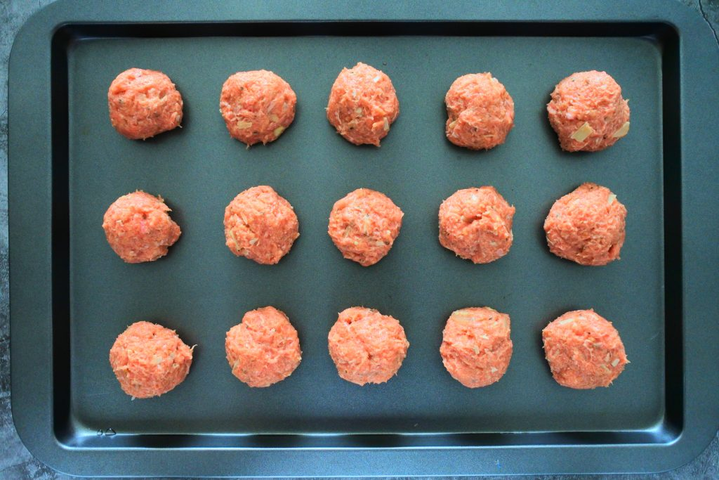 An overhead image of a baking tray with fifteen uncooked turkey meatballs