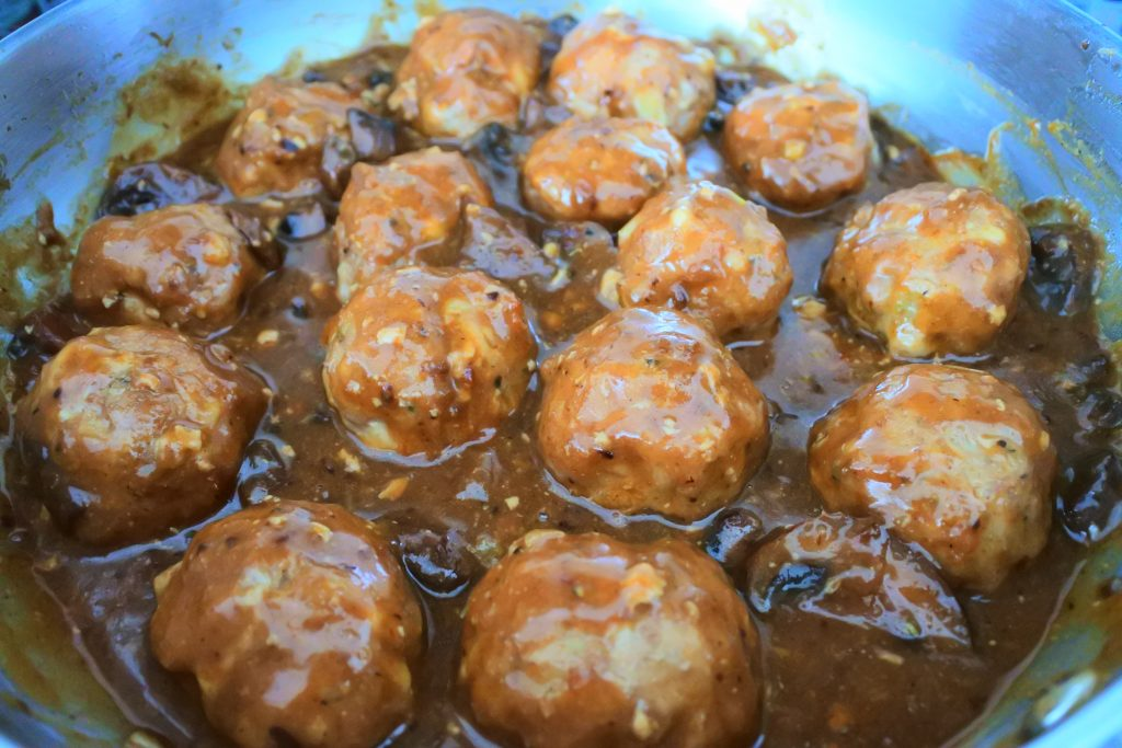 A close up image of a saute-pan of turkey meatballs smothered in a mushrooms and onion gravy