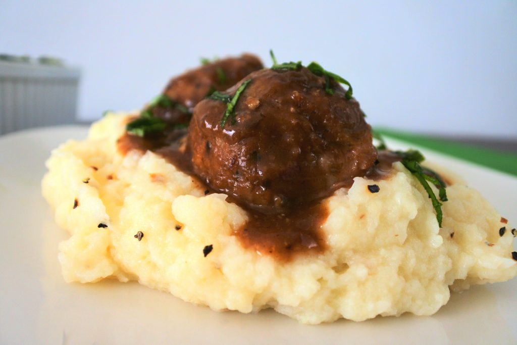 A close up image of a serving of mashed cauliflower topped with two Salisbury meatballs in gravy.