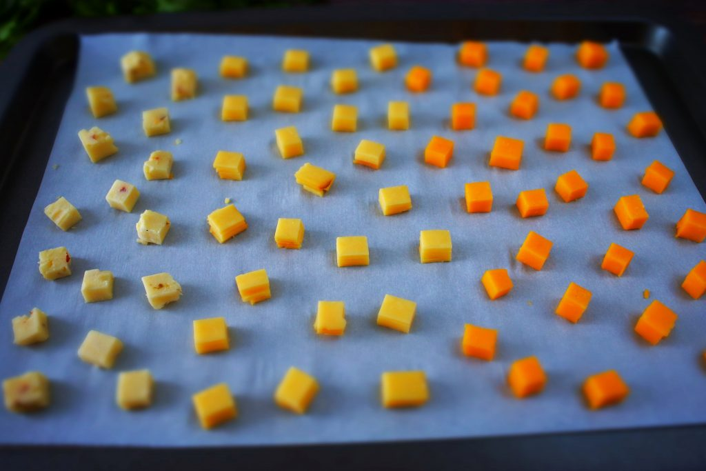An over head image of a tray of parchment paper with small cubes of cheese evenly spaced out on it