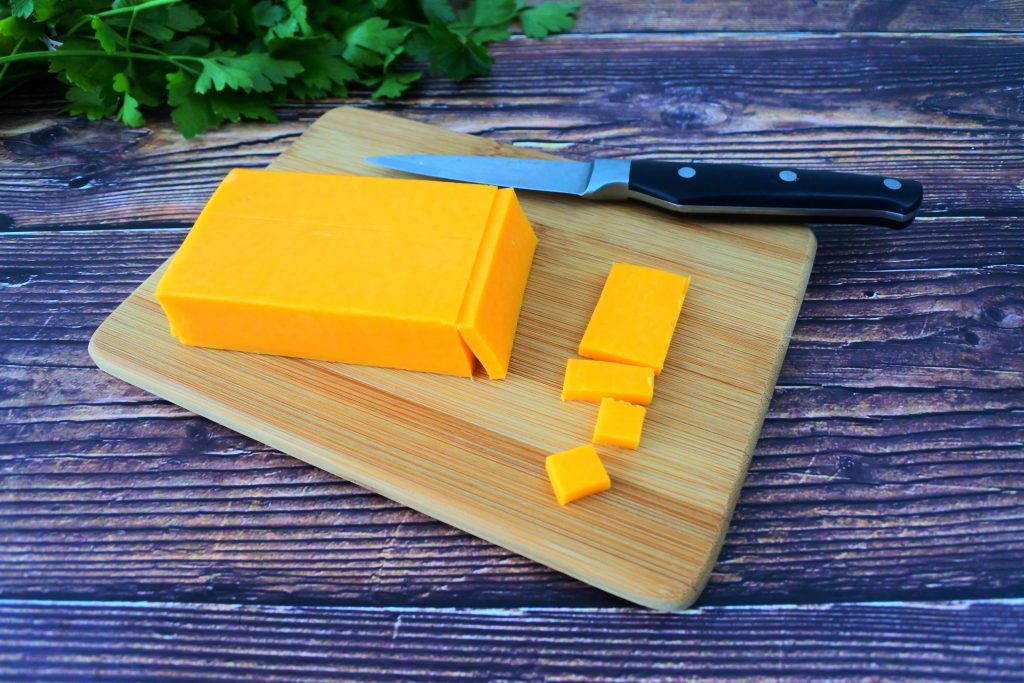An overhead image of a block of cheddar cheese on a wooden plank with a knife and fresh greens in the top corner