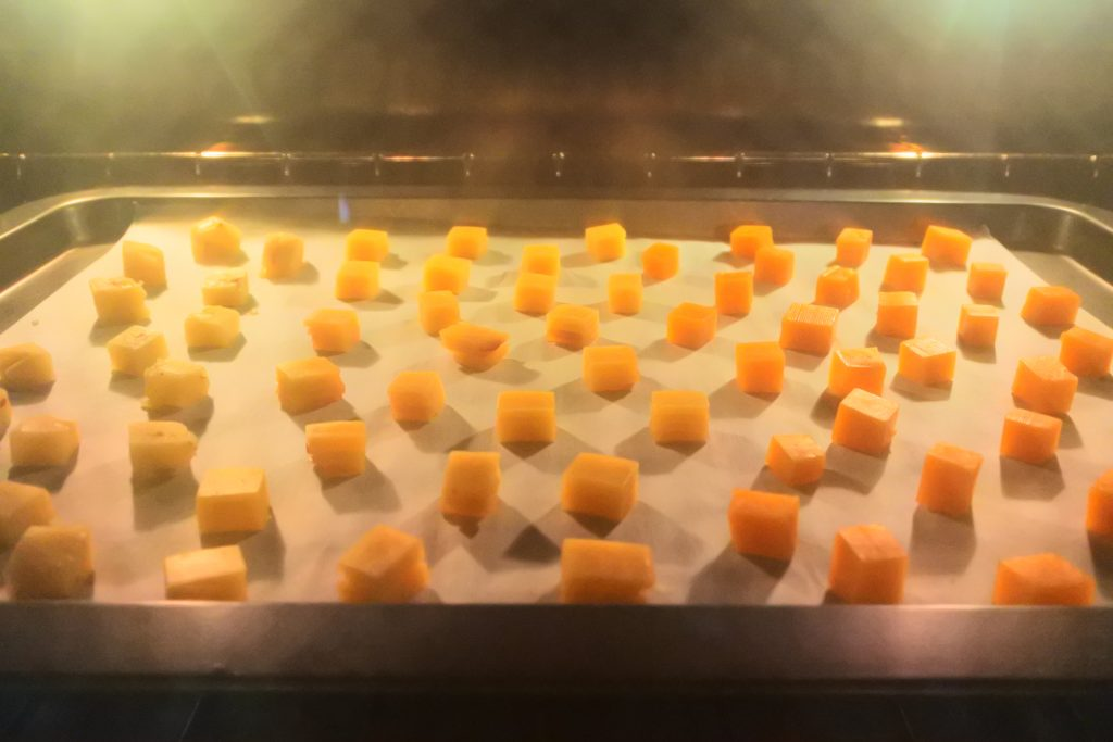 A head on image of a tray of small cheese cubes on parchment paper in an oven