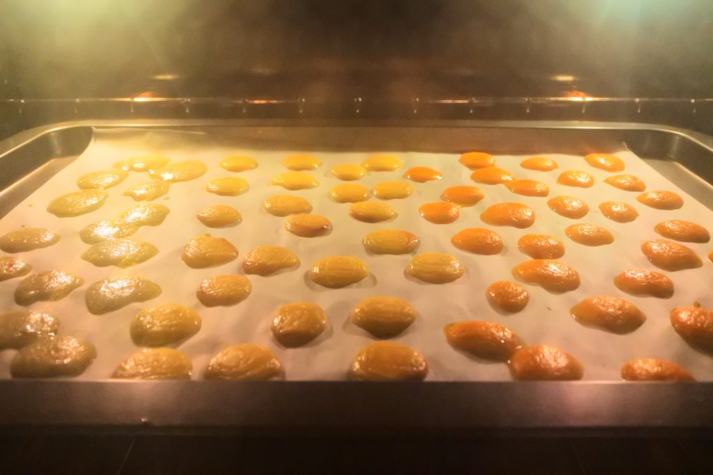 A head on image of melted cheese cubes on a parchment lined baking tray in an oven