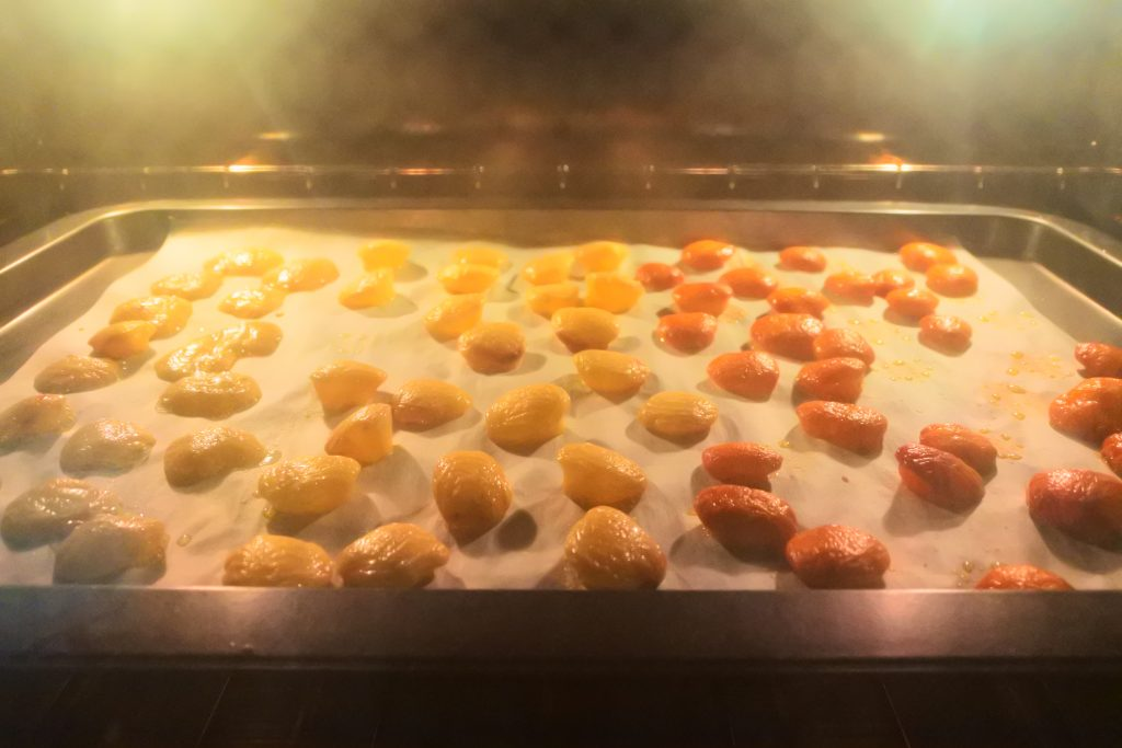 A head on image of popped cheese bits on a parchment lined baking tray in an oven