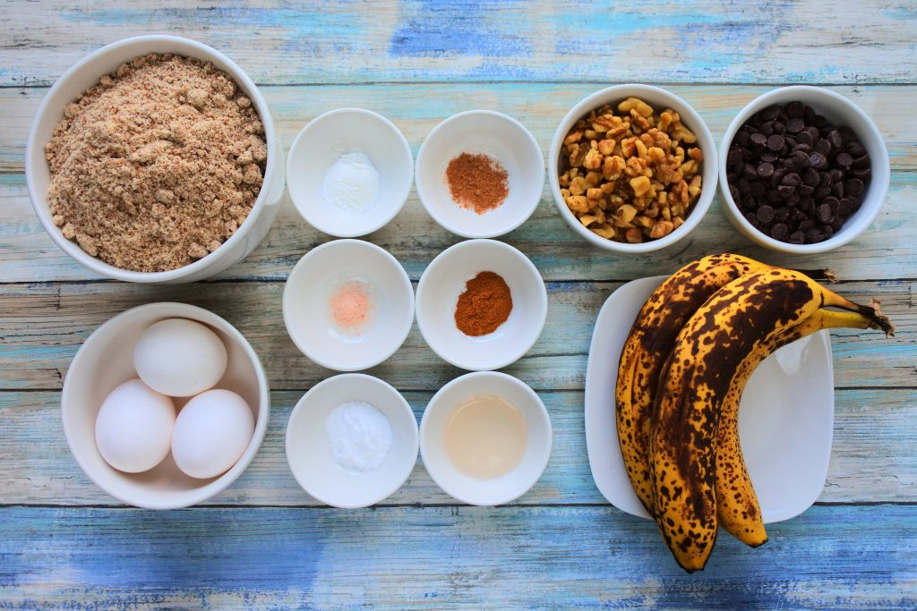 An overhead image of dishes containing ingredients for banana nut dark chocolate muffins including almond flour, eggs, bananas, baking powder, baking soda, nutmeg, cinnamon, salt, vanilla extract, chopped walnuts and dark chocolate chips.