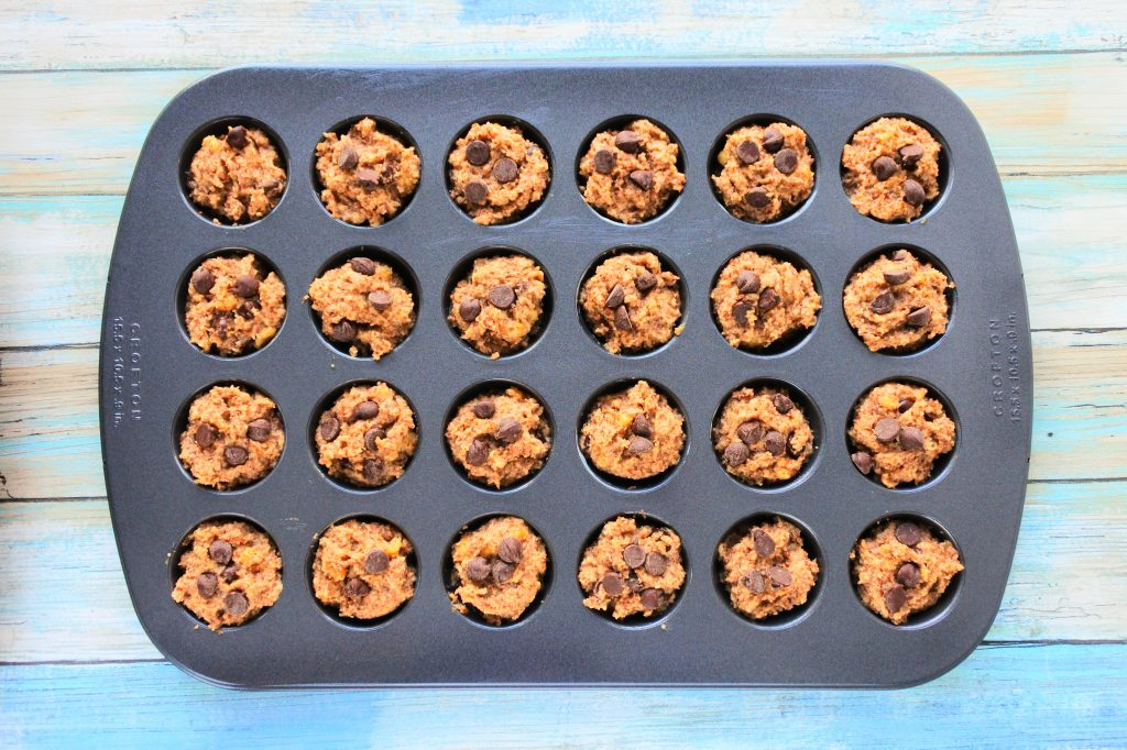 An overhead image of a mini muffin tray filled with banana nut dark chocolate muffin batter