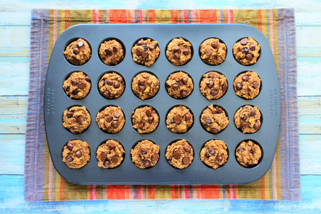An overhead image of a mini muffin tray of baked banana nut dark chocolate muffins